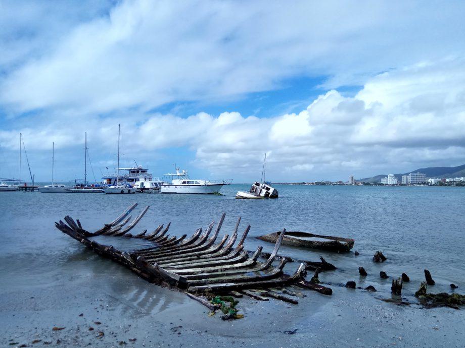 На дальнем плане еще не совсем затонувшая лодка
